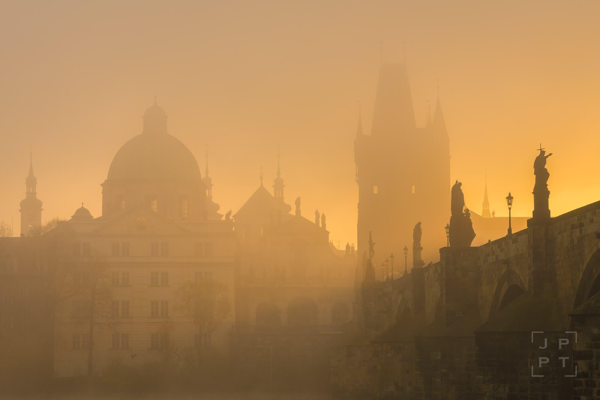 Charles bridge with mist at sunrise, Prague